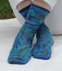 Meandering Mesh - Panels of lace rise diagonally up to the left from the sole, making them meander on the foot but settle into orderly spirals on the leg.